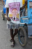 MADAGASCAR, Mananjary, rickshaw puller with Promo T-shirt of President Hery Rajaonarimampianina  / MADAGASKAR Mananjary, Rickscha Kuli mit zerschlissenem Promotion T-shirt von  Praesident Hery Rajaonarimampianina