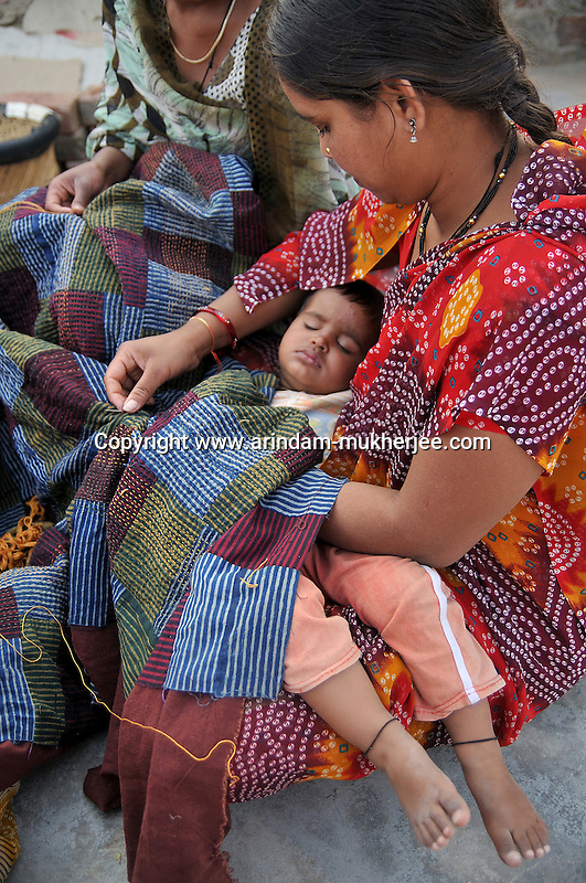 A mother doing her assignment given by Sadhna with her child on her lap. Ratakhet slum in Udaipur, Rajasthan, India. 24.1.2011. Arindam Mukherjee