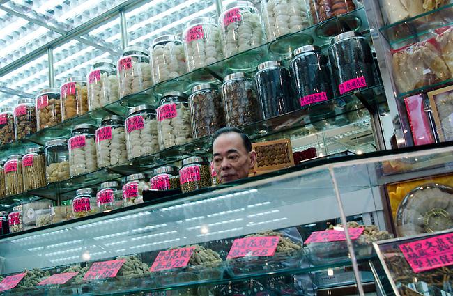 Hong Kong urban scene - man selling chinese herbs, looks like head is jar