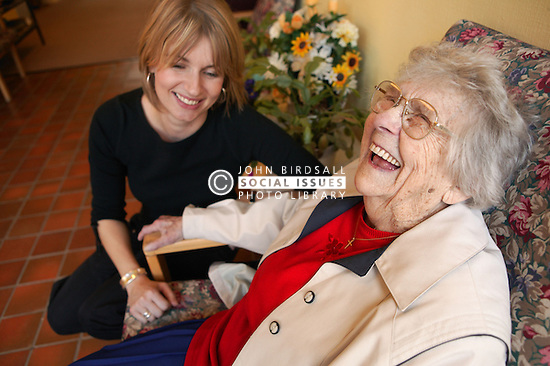 Elderly woman and carer laughing together in sheltered accommodation,