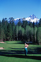 A golfer tees off at the 14th hole with trees and a mountain in the backgound. Black Butte Ranch, Oregon.