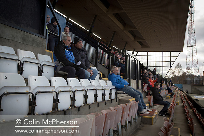Spectators in the grandstand watching the second-half action at the Commonwealth Stadium at Meadowbank during the Scottish Lowland League match between Edinburgh City (white shirts) and city rivals Spartans, which was won by the hosts by 2-0. Edinburgh City were the 2014-15 league champions and progressed to a play-off to decide whether there would be a club promoted to the Scottish League for the first time in its history. The Commonwealth Stadium hosted Scottish League matches between 1974-95 when Meadowbank Thistle played there.