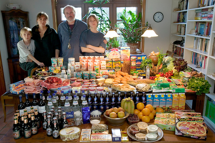 (MODEL RELEASED IMAGE). The Melander family: Jörg, and Susanne, with sons Kjell, and Finn, in the dining room of their home in Bargteheide, Germany, with a week's worth of food. The Melander family is one of the thirty families featured in the book Hungry Planet: What the World Eats (p. 132).