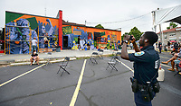 Joseph Hall, an officer with the Fayetteville Police Department, takes photographs Saturday, June 20, 2020, as Art Ventures artists complete a mural during the Fayetteville in Living Color event in the parking lot of St. Paul's Episcopal Church in Fayetteville. The event was held to register residents to vote, to support the Black Lives Matter movement and to foster community unity. Visit nwaonline.com/200621Daily/ for today's photo gallery.<br /> (NWA Democrat-Gazette/Andy Shupe)