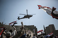 In this Friday, Jul. 26, 2013 photo, pro Sisi protesters watch to an army helicopter flying over Tahrir square during a rally in Cairo. (Photo/Narciso Contreras).