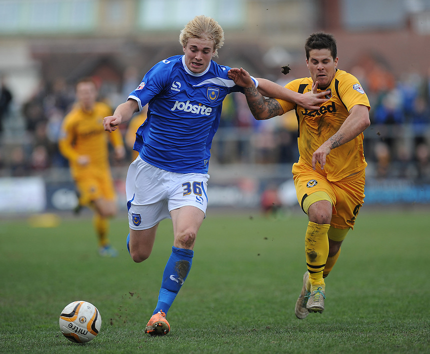 Portsmouth's Jack Whatmough vies for possession with Newport County's Danny Crow<br /> <br /> Photo by Ashley Crowden/CameraSport<br /> <br /> Football - The Football League Sky Bet League Two - Newport County AFC v Portsmouth - Saturday 29th March 2014 - Rodney Parade - Newport<br /> <br /> &copy; CameraSport - 43 Linden Ave. Countesthorpe. Leicester. England. LE8 5PG - Tel: +44 (0) 116 277 4147 - admin@camerasport.com - www.camerasport.com