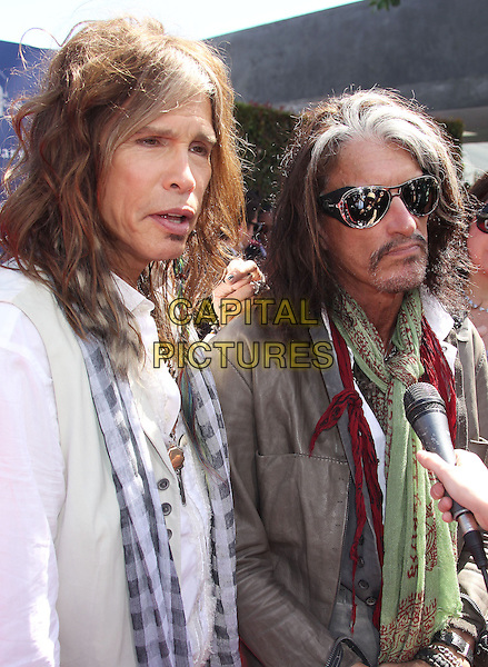 Steven Tyler & Joe Perry of Aerosmith.10th Annual John Varvatos Stuart House Benefit held at John Varvatos Boutique, Beverly Hills, California, USA..March 10th, 2013.half length jacket jeans denim white green blue check scarf grey gray cane sunglasses shades moustache mustache facial hair microphone mouth open.CAP/ADM/RE.©Russ Elliot/AdMedia/Capital Pictures.