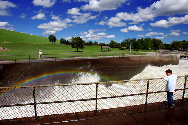 Isaac Glanz, 8, of Des Moines west watches a rainbow formed from water spray at the Saylorville Lake spillway.