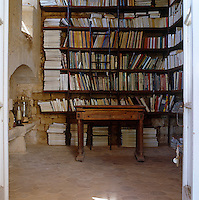 The small library retains much of its original stonework with simple mahogany shelves placed against the wall