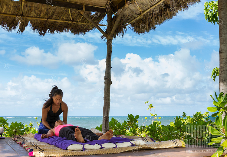 A woman gives a massage to another woman in an outdoor grass hut on the beach on O'ahu.