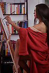Artistic sensual portrait of a beautiful asian woman in red kimono, Japanese sumi-e artist with an easel, painting on rice paper with a brush in her home studio Image © MaximImages, License at https://www.maximimages.com