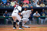 San Antonio Missions first baseman Luis Domoromo (7) slides safely into home past catcher Zane Evans (30) during a game against the NW Arkansas Naturals on May 30, 2015 at Arvest Ballpark in Springdale, Arkansas.  San Antonio defeated NW Arkansas 5-1.  (Mike Janes/Four Seam Images)