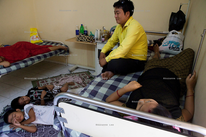 """Ganesh visits his wife Diksha as she lies in her shared surrogate's room on the 3rd floor of the Akanksha Infertility Clinic, Anand, Gujarat, India...Clockwise: Ganesh Gurunja, 28 (yellow, top left); Diksha Gurunja, 28 (top right); 2 boys, 11 and 8 (below).Nepali couple based in Anand, Gujarat..- Ganesh is a merchant operator and earns Rs. 6,000-7,000 a month but is not working right now. He's taking care of the kids and home while Diksha is pregnant with her second surrogacy..- The education expenses of the children are alone Rs. 20,000 a year. .- They used to rent a three-bedroom apt. for Rs. 2,000 per month, which they bought for Rs. 3.5 lakhs with money from Diksha's first surrogacy..- Both the surrogacies were for Japanese couples...Quotes.""""You have to lose something to gain something. And what we gain is a lot more than what we lose. For nine months we live like this away from family but with the money, we could get his [Ganesh's] kidney stone operation done, buy a house, a bike, send children to English-medium schools, and eat, wear and sleep well. There are no problems now."""" - Diksha..The Akanksha Infertility Clinic is known internationally for its surrogacy program and currently has over a hundred surrogate mothers pregnant in their environmentally controlled surrogate houses. .Photo by Suzanne Lee"""