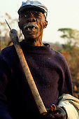 Chaleli, Zambia. Toothless man wearing a cap with a wooden handled axe tool over his shoulder.