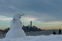 A snowman is seen from Weehawken while the One Word Trade Center and the Hudson river are photographed  after the pass of the winter storm JONAS, in New York, 01/24/2016. Photo by VIEWpress