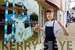 Joe Cahillane outside of Cahillane's Butchers shop window in Killorglin decorated for Puck Fair.