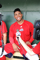 Second baseman Yoan Moncada (24) of the Greenville Drive, right, talks to the media before a game against the Lexington Legends on Monday, May 18, 2015, at Fluor Field at the West End in Greenville, South Carolina. Moncada, a 19-year-old prospect from Cuba, made his professional debut tonight in the Red Sox organization. (Tom Priddy/Four Seam Images)
