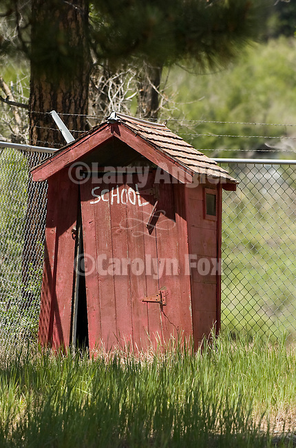 "Red wooden outhouse with cyclone fence, ""School"" painted on the door, Colorado Rockys"