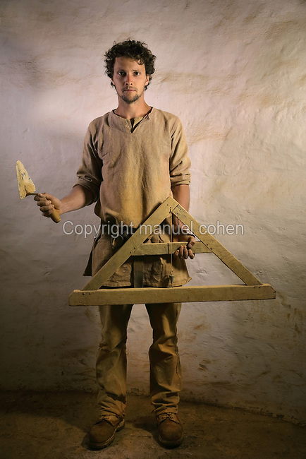 Baptiste Fabre, bricklayer on the Guedelon project since 01/04/2014, wearing medieval costume and holding a trowel and A-frame plumb line, at the Chateau de Guedelon, a castle built since 1997 using only medieval materials and processes, in Treigny, Yonne, Burgundy, France. The Guedelon project was begun in 1997 by Michel Guyot, owner of the nearby Chateau de Saint-Fargeau, with architect Jacques Moulin. It is an educational and scientific project with the aim of understanding medieval building techniques and the chateau should be completed in the 2020s. Picture by Manuel Cohen