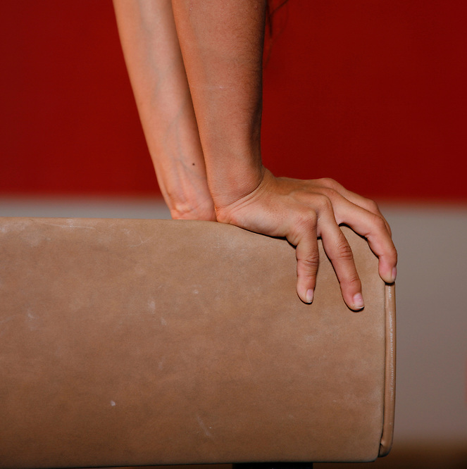 MARCH 21, 2007; TAMPA, FLORIDA;  A young gymnast grips a balance beam during a gymnastics training session. Photo by Matt May