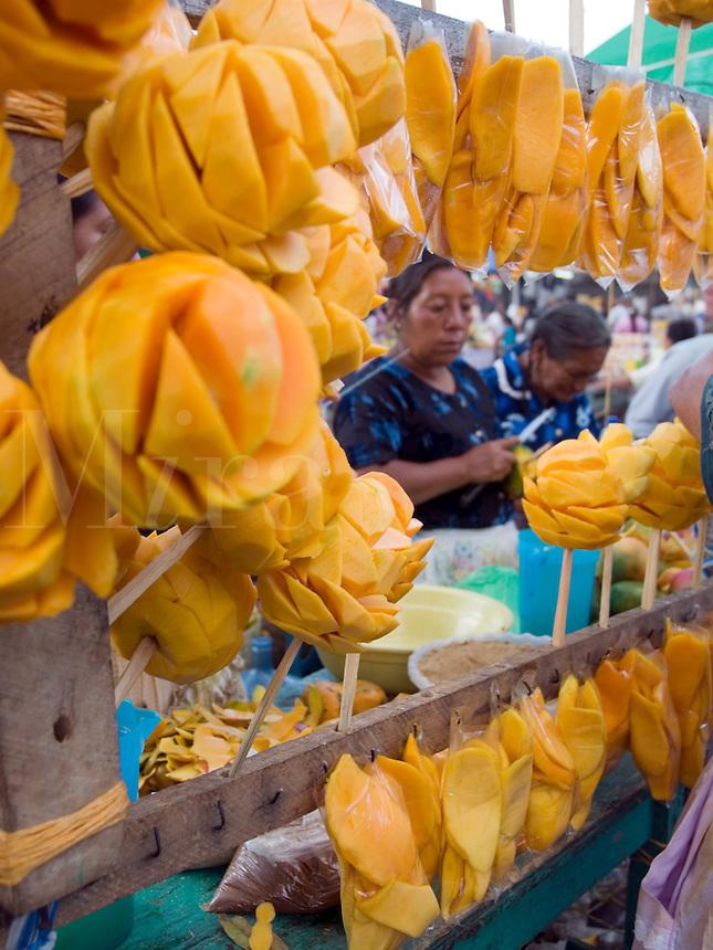 Antigua, Guatemala. Freshly cut fruit on sticks for sale in the city market.