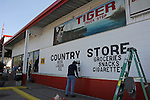 Men paint the exterior of the Tiger Conoco gas station in Grosse Tete, Louisiana on April 14, 2009.  A tiger that paces back and forth all day in a cage several meters long at the end of the Tiger Conoco gas station  is the primary attraction in Grosse Tete; a sign requesting donations asks visitors to help keep the tiger in his tightly enclosed space that in no way resembles his habitat.