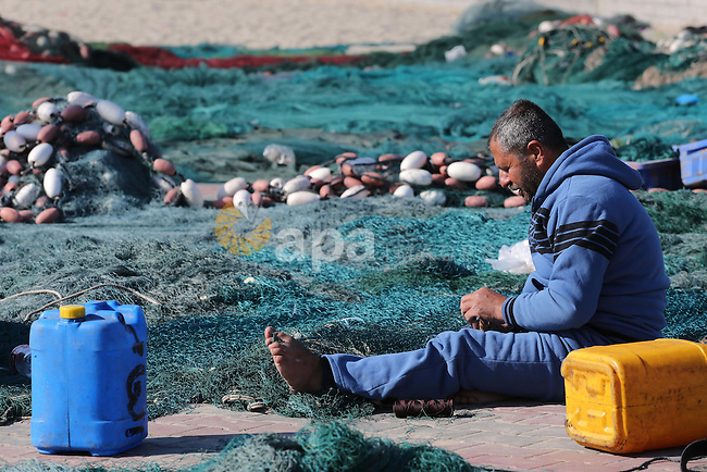 A Palestinian fisherman repairs his nets at the coast of Gaza city on Dec. 22, 2015. Israeli naval forces early Tuesday detained 14 Palestinian fishermen off the coast of the Gaza Strip near Beit Lahiya and seized their boats, local officials said. Photo by Mohammed Asad