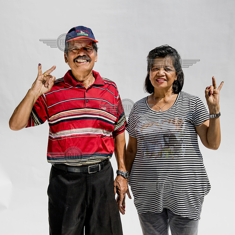 A couple flash a two fingered sign, symbolising Indonesian presidential candidate Jokowi's candidacy number after they cast their votes at a polling station in Jakarta.