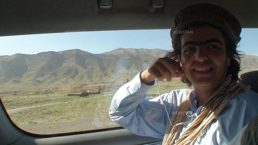 """AFGHANISTAN - VALLEE DU PANJSHIR - 18 aout 2009 : .Sortie de la Vallee du Panjshir, route du Nord de Kaboul. Delazad Deghati. On apercoit par les vitres de la voiture des carcasses de chars pris aux russes par les Moudjahidin du Commandant Massoud lors de leurs assauts pendant la guerre d'Afghanistan de 1979 - 1989. .La photographie appartient a la serie """"Il etait une fois l'Empire Russe"""". ..AFGHANISTAN - PANJSHIR VALLEY -  August 18th, 2009 : Exit from the Panjshir Valley on the highway north of Kabul..Delazad Deghati. Through the car window remnants of Russian tanks seized by Commander Massoud's mujahideen in the Afghan war of 1979-1989 can be seen..The photograph is part of the series """"Once Upon a Time, the Russian Empire."""""""