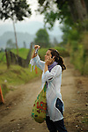 Bogota yoga teacher Claduia Patricia Sanchez works her cell phone and camera on a country road in the coffee region of Salento, Colombia.