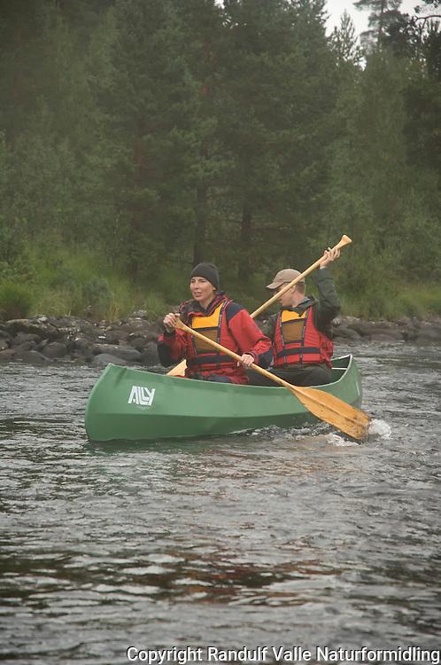 Mann og dame i Ally Kano på Håelva. ---- Man and woman in Ally canoe on river Håelva.