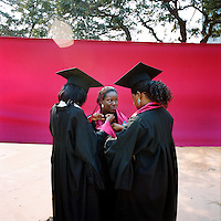 Three female students, wearing gowns and motar boards, help each other with their dress prior to their graduation ceremony at Agostinho Neto University's law faculty.