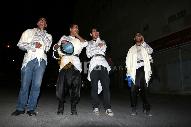 Palestinians youths 'Mesaharaty' use  a traditional drum to wake up people for their Suhoor, in the West Bank city Ramallah, on, Aug. 22, 2011. Muslims throughout the world are celebrating the holy fasting month of Ramadan, the holiest month in Islamic calendar, refraining from eating, drinking, and smoking from dawn to dusk. Photo by Issam Rimawi