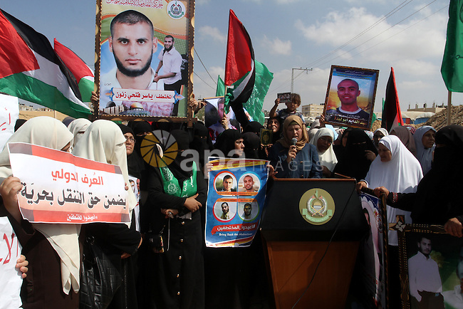 Families of Palestinians who were abducted by gunmen is the northern region of Egypt's Sinai peninsula in August, hold portraits of their loved ones as they take part in a demonstration calling for their release at the Rafah border with Egypt in the southern Gaza Strip, on October 14, 2015. Gunmen in Egypt boarded a bus carrying Palestinians from Cairo to Gaza and seized four of the passengers before letting the others continue, Hamas officials in the strip said. Photo by Abed Rahim Khatib
