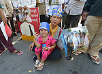 "A woman and her daughter participate in a vigil outside a Phnom Penh court on December 14, 2012, during a hearing in which judges denied an appeal by Mam Sonando, a Cambodian radio journalist and human rights activist. Mam Sonando was sentenced in October 2012 to 20 years in prison for ""insurrection,"" despite local and international calls for his release."