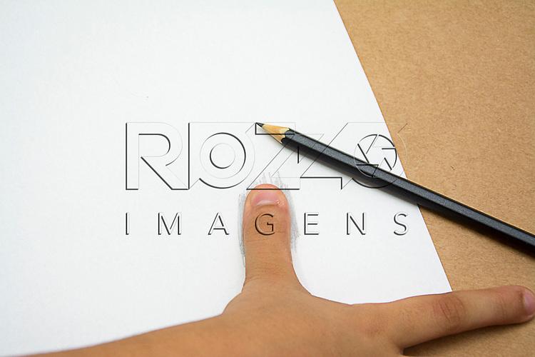 Mão de criança posicionando o polegar direito em uma área de uma folha de papel branca previamente pintada com lápis grafite, São Paulo - SP,12/2015