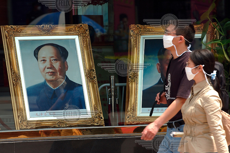 © Dermot Tatlow / Panos Pictures..China. April 2003...A couple wearing face masks to protect against the SARS virus, passing a portrait of Chairman Mao on display in a window.