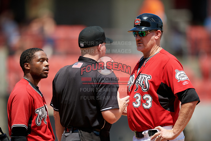 Carolina Mudcats manager Joe Ayrault (33) argues a call with umpire Kyle Nichol as Devin Hairston (6) looks on during a Carolina League game against the Winston-Salem Dash on August 14, 2019 at Five County Stadium in Zebulon, North Carolina.  Winston-Salem defeated Carolina 4-2.  (Mike Janes/Four Seam Images)