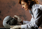 Archaeologist cleaning an Egyptian style head from a statue from Villa Hadriana, Italy