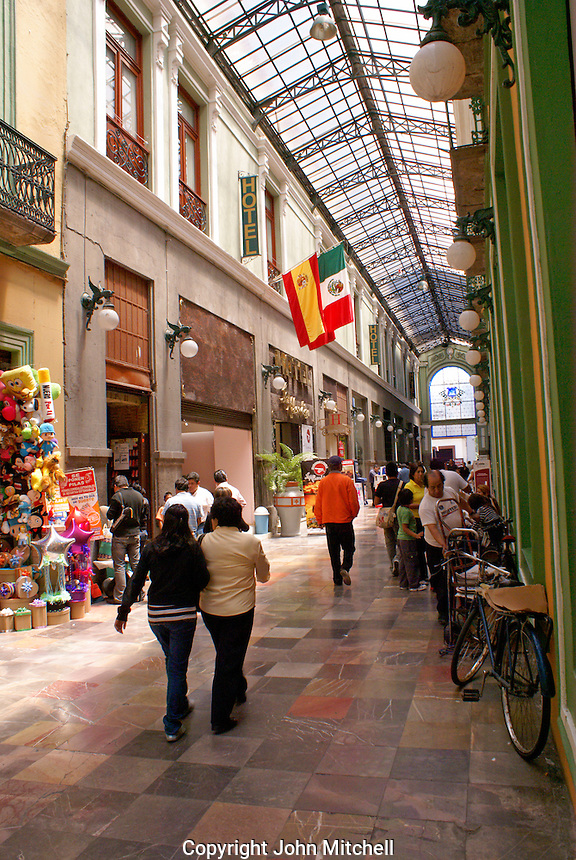 People in a covered pedestrian walkway and shopping mall, Puebla, Mexico. The historical center of Puebla is a UNESCO World Heritage Site.