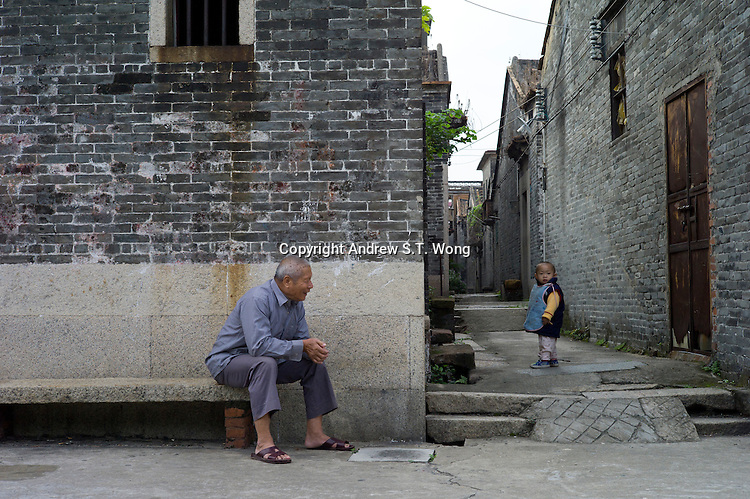 A grandfather plays with his grandson at the ancient Huangxi village in Dali of Nanhai district in Foshan city, Guangdong province, November 11, 2011.