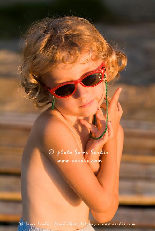 Little blond girl pausing at sunrise, Cienfuegos, Cuba.