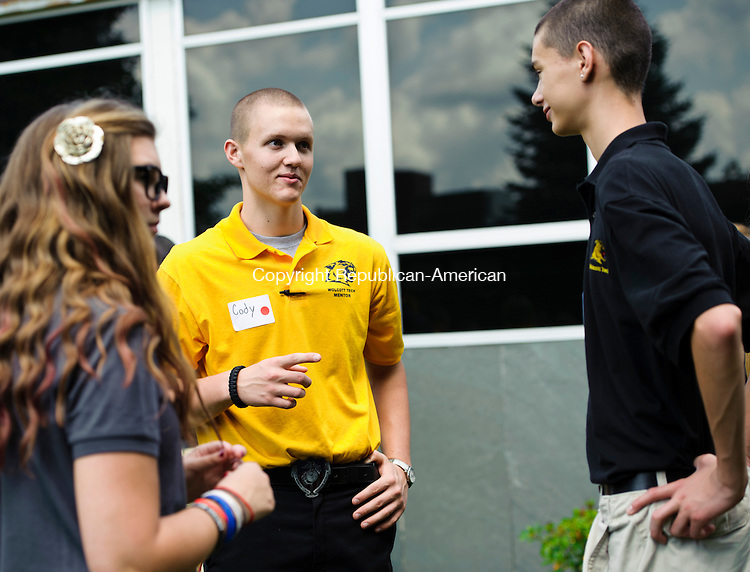 TORRINGTON, CT - 28 August 2013-082813EC03--   Cody Murphy, a senior wearing a yellow shirt, talks to two incoming freshman Wednesday at Oliver Wolcott Technical High School. Anastasia Lazzaro (L) and Joshua McCue (R) are among the ninth graders who have been assigned to Murphy, who applied to be a mentor. The new program is to help freshmen navigate classes and easily get information from the school's veteran students. Erin Covey Republican-American.