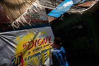 """A Colombian sign painter apprentice writes with a brush while working on music party posters in the sign painting workshop in Cartagena, Colombia, 15 April 2018. Hidden in the dark, narrow alleys of Bazurto market, a group of dozen young men gathered around José Corredor (""""Runner""""), the master painter, produce every day hundreds of hand-painted posters. Although the vast majority of the production is designed for a cheap visual promotion of popular Champeta music parties, held every weekend around the city, Runner and his apprentices also create other graphic design artworks, based on brush lettering technique. Using simple brushes and bright paints, the artisanal workshop keeps the traditional sign painting art alive."""