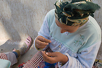 A Moroccan woman makes toggle buttons with blue thread so quickly her hands blur, near Sefrou, Morocco