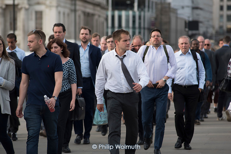 City of London workers walk across London Bridge during the evening rush hour