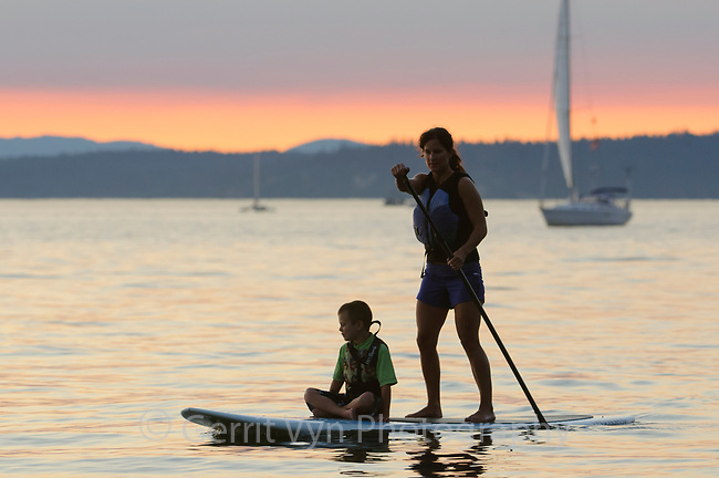 Athletic woman paddleboarding with a child in the waters of Puget Sound. Seattle, Washington.