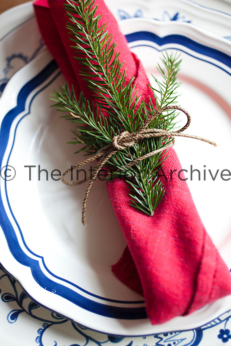 Detail of a table setting with a hand-woven linen napkin decorated with a sprig of spruce wrapped in string