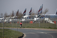 BNPS.co.uk (01202 558833)<br /> Pic: CorinMesser/BNPS<br /> <br /> A cyclist gets her excercise as she rides past the BA planes<br /> <br /> Fleet of BA planes still arriving at Bournemouth Airport today (Thursday)<br /> <br /> Bournemouth Airport has today been turned into a plane park for British Airways aircraft that have nowhere else to go during the coronavirus pandemic.<br /> <br /> More than 30 BA aircraft are expected to arrive in Dorset following the collapse of global air travel.<br /> <br /> Major airports like Heathrow and Gatwick are already full with grounded planes.<br /> <br /> With no room left to park them BA is having to fly its A320 planes to regional airports like to Bournemouth.