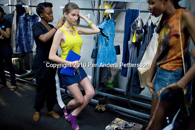JOHANNESBURG, SOUTH AFRICA - MARCH 26: Assistants prepare a model backstage before a fashion show at the South African fashion week on March 26, 2010, Turbine Hall in central Johannesburg, South Africa. Buyers and celebrities watched the 3 day fashion week, a biannual event. (Photo by Per-Anders Pettersson)